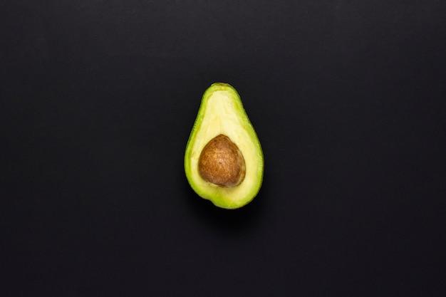 Przyrodni avocado na czarnym tle. pojęcie wyborów żywieniowych. przydatne lub szkodliwe jedzenie. minimalizm. leżał płasko, widok z góry.