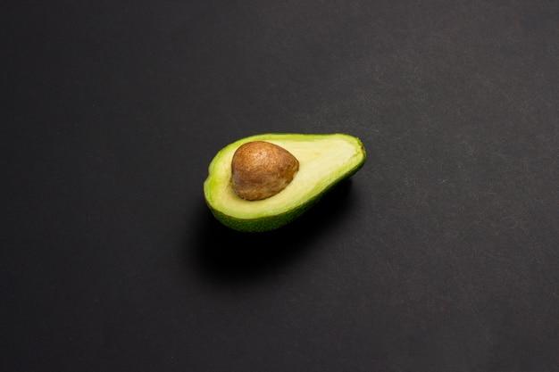 Przyrodni avocado na czarnym tle. pojęcie wyborów żywieniowych. przydatne lub szkodliwe jedzenie. minimalizm.