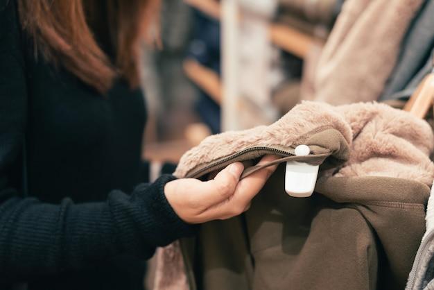 Przyrodni ciało strzelał szczęśliwa azjatykcia młoda kobieta patrzeje odzież z naramienną torbą