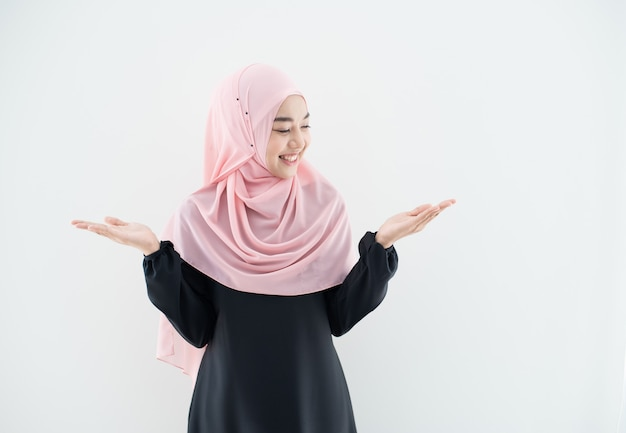 Przyrodni długość portret azjatykcia piękna muzułmańska młoda kobieta jest ubranym biznesowego ubiór i hijab z mieszanymi pozami i gestami odizolowywającymi na szarości ścianie. nadaje się do technologii, tematu finansowania biznesu.