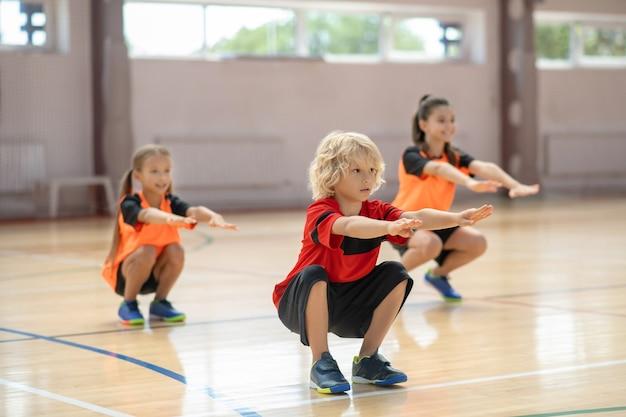 Przysiady. trójka dzieci ćwiczy na siłowni i robi przysiady