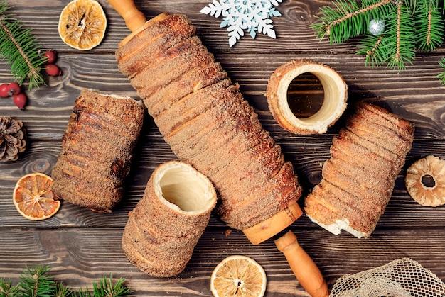 Przysmak z ciasta trdelnik. ciasto wypiekane na szaszłyku i węglu drzewnym z dodatkiem cukru, cynamonu i wanilii. świąteczne słodycze, uliczne jedzenie. kuchnia czeska i morawska.