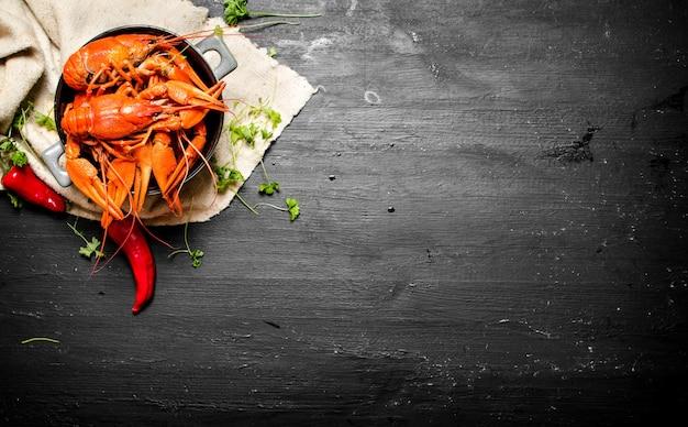 Przysmaki kulinarne. gotowana raki z ziołami i ostrą papryką. na czarnej tablicy.