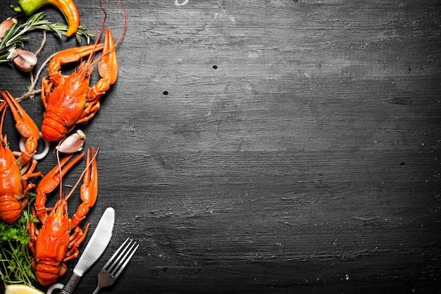 Przysmaki kulinarne. świeżo gotowana raki z przyprawami i ziołami. na czarnej tablicy.