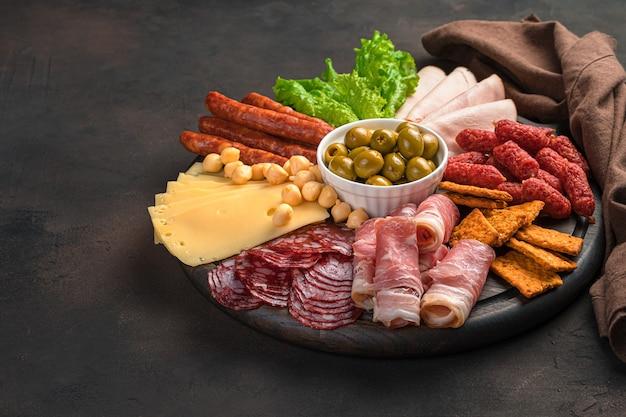 Przysmaki mięsno-serowe z ziołami i oliwkami na brązowym biurku. widok z boku, poziomy.