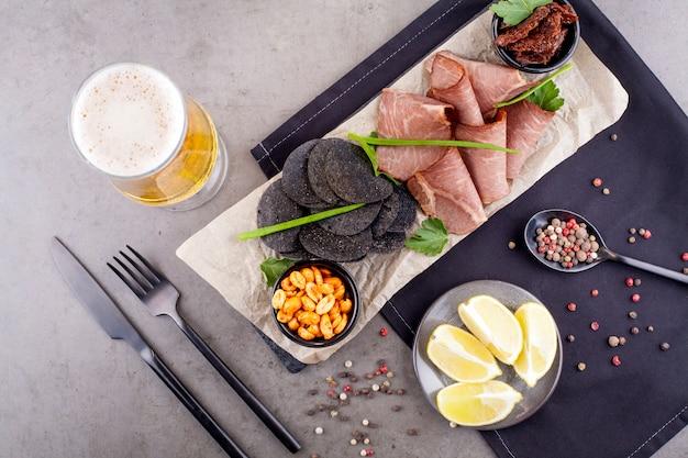 Przystawka do piwa, składająca się z orzeszków ziemnych, mięsa i frytek, ozdobiona pieprzem, sztućce. pojęcie przekąsek do piwa.