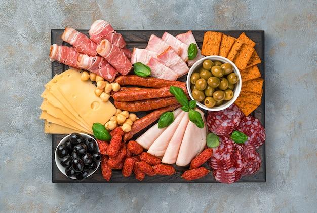 Przystawka mięsna, ser i oliwki na prostokątnej desce do krojenia