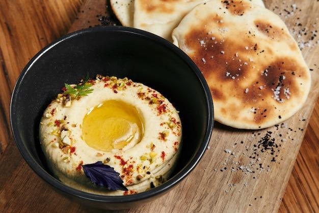 Przystawka z bliskiego wschodu hummus podawany ze świeżym chlebem pita i ziołami na drewnianym tle widok z góry