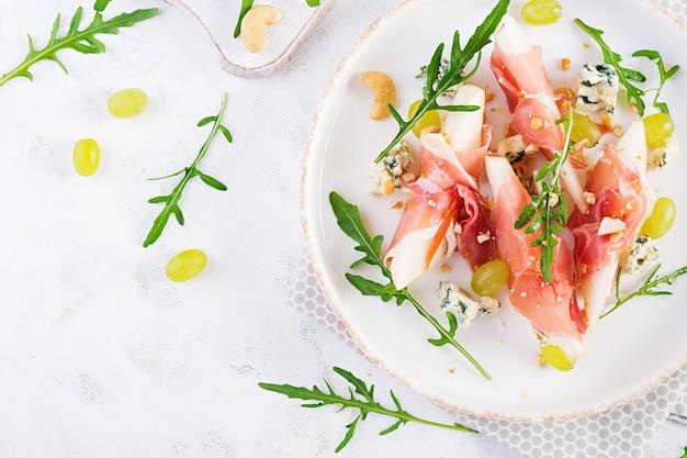 Przystawka z gruszką, serem pleśniowym i szynką prosciutto na wakacje na białym talerzu. widok z góry, układ płaski