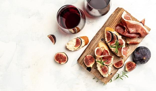 Przystawki. antipasti, przekąski i wino. kanapka z prosciutto, twarogiem i figami. baner, menu, przepis na tekst, widok z góry.