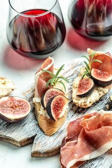 Przystawki, kanapka z prosciutto, serkiem śmietankowym i figami. przekąski antipasti i czerwone wino w kieliszkach. zestaw autentycznych tradycyjnych hiszpańskich tapas. widok z góry.