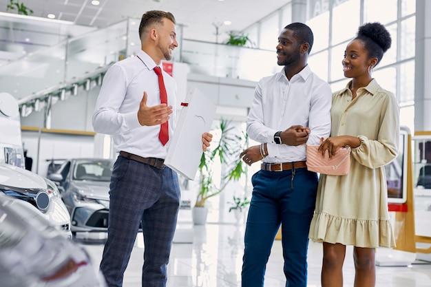 Przystępny dealer samochodów kaukaskich konsultuje się z klientami