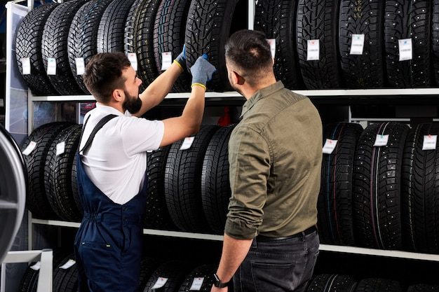 Przystępny mechanik samochodowy w mundurze pomaga klientowi w wyborze, młody mężczyzna rasy kaukaskiej przyszedł kupić nowe opony do samochodu. czynny