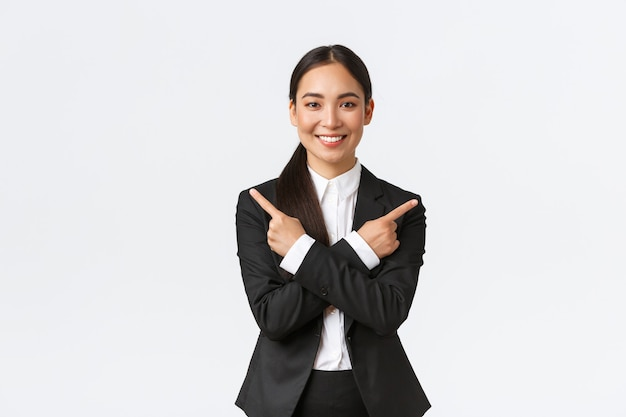 Przystojna azjatycka sprzedawczyni proponuje dwie możliwości. atrakcyjna bizneswoman w czarnym garniturze, wskazując palcami na boki, ma kilka wariantów, pomaga w podjęciu decyzji, stoi na białym tle