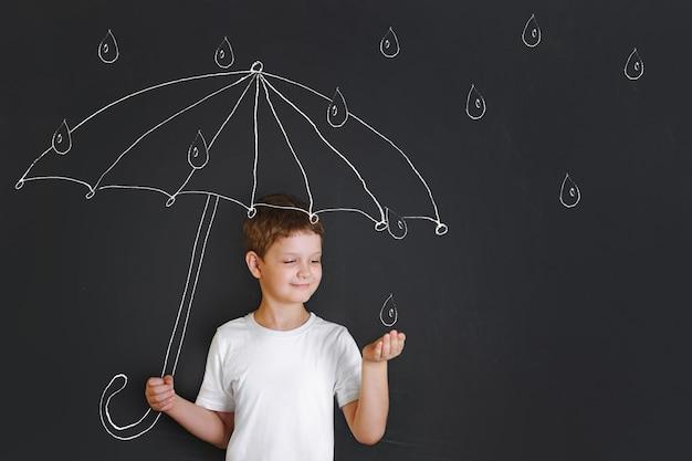 Przystojna chłopiec pod kredowym rysunkowym parasolem