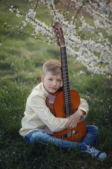 Przystojna chłopiec robi muzyce bawić się gitarę siedzi na trawie w letnim dniu.