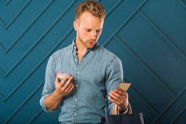 Przystojna dorosła samiec sprawdza jego telefon