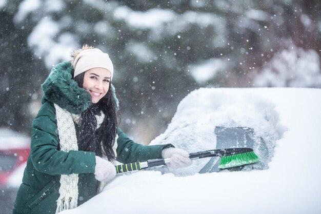 Przystojna dziewczyna odśnieża samochód w śnieżny zimowy dzień.
