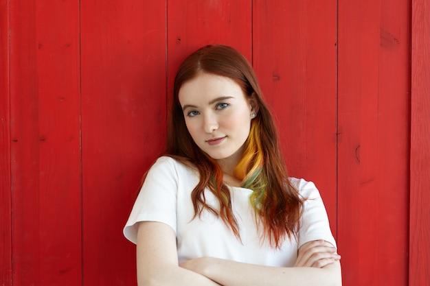 Przystojna dziewczyna z kolorowymi pasmami w imbirowych długich włosach na sobie biały top, patrząc z założonymi rękami. strzał pół ciała zielonookiej studentki ze skrzyżowanymi rękami