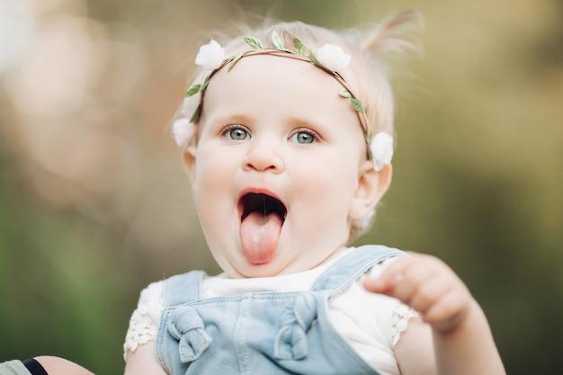 Przystojna dziewczynka z krótkie jasne włosy i ładny uśmiech w białej sukni siedzi na trawie w parku latem i uśmiecha się