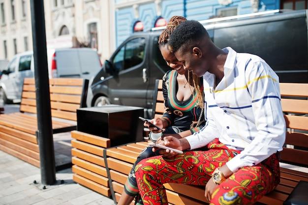 Przystojna elegancka amerykanin afrykańskiego pochodzenia para siedzi na ławce przy miastem z telefonami komórkowymi przy rękami.