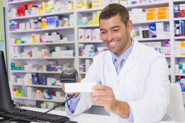 Przystojna farmaceuta skanuje medycyny pudełko