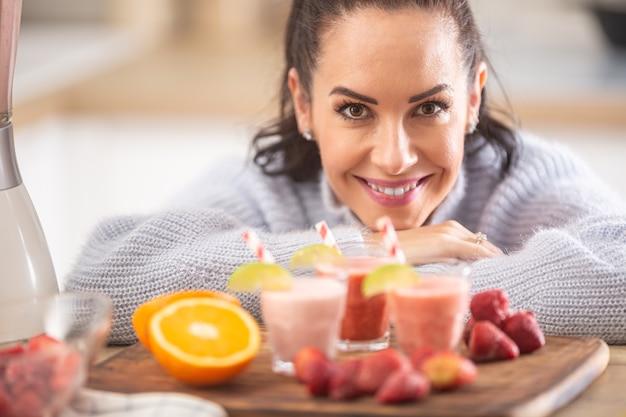 Przystojna kobieta ciesząca się domowymi koktajlami owocowymi w kuchni.