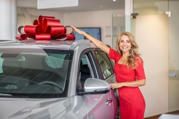 Przystojna kobieta ciesząca się z prezentowanego samochodu