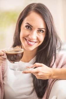 Przystojna kobieta cieszy się filiżanką gorącej czekolady.