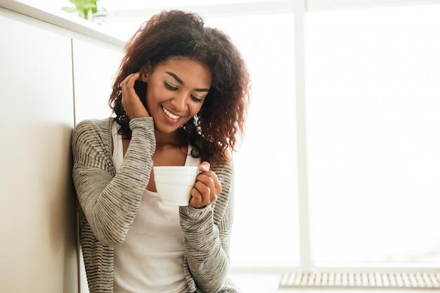 Przystojna kobieta z filiżanką herbaciany obsiadanie na podłoga