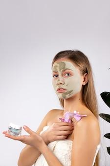 Przystojna kobieta z zieloną maseczka na twarz oddział orchidei i śmietany w dłoniach