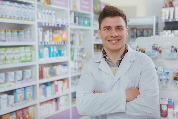 Przystojna męska farmaceuta pracuje przy jego apteką
