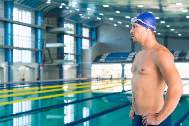 Przystojna męska pływaczka patrzeje daleko od