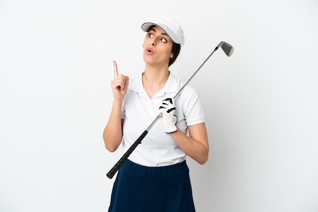 Przystojna młoda golfistka na białym tle myśląca o pomyśle wskazującym palec w górę