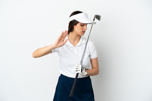 Przystojna młoda golfistka na białym tle robi gest zatrzymania i rozczarowana