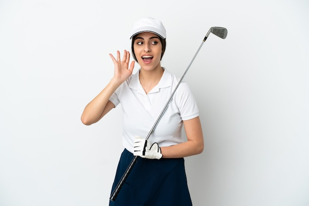 Przystojna młoda golfistka na białym tle słuchając czegoś, kładąc rękę na uchu