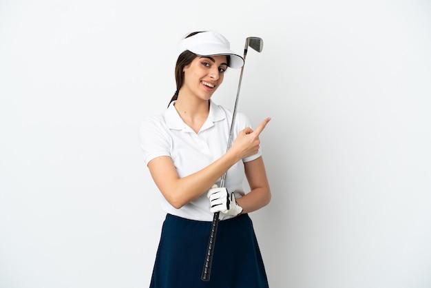 Przystojna młoda golfistka odizolowana na białym tle wskazująca do tyłu