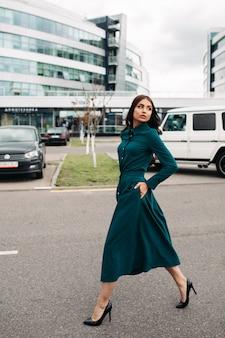 Przystojna młoda kaukaska kobieta z ładną buzią w pięknej zielonej sukience o długości poniżej kolan idzie na ulicę