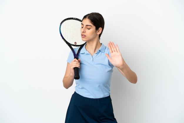 Przystojna młoda tenisistka kaukaska kobieta na białym tle robiąca gest zatrzymania i rozczarowana