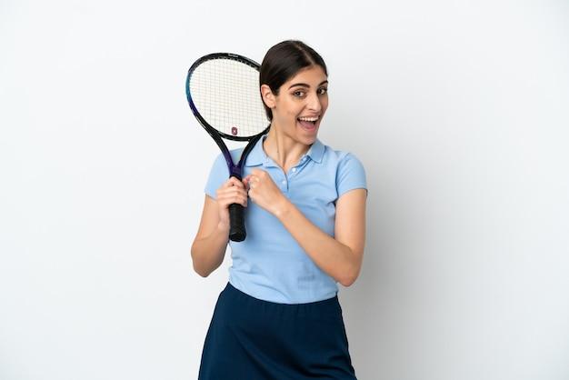 Przystojna młoda tenisistka kaukaska kobieta na białym tle świętuje zwycięstwo