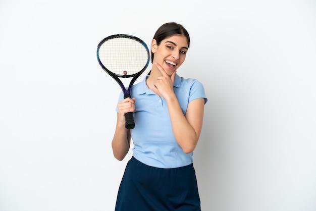 Przystojna młoda tenisistka kaukaska kobieta na białym tle szczęśliwa i uśmiechnięta