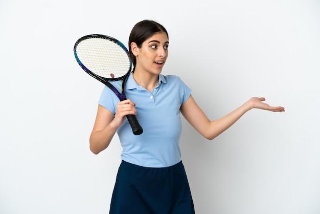 Przystojna młoda tenisistka kaukaska kobieta na białym tle z wyrazem zaskoczenia, patrząc z boku