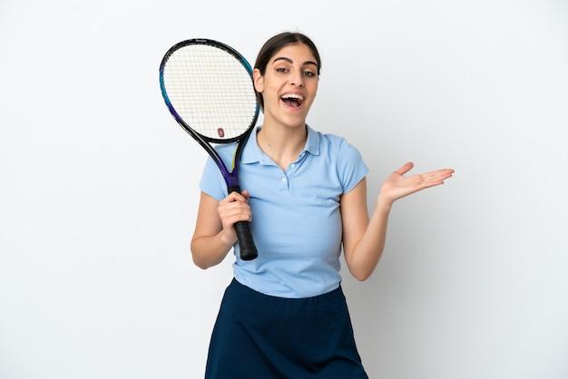 Przystojna młoda tenisistka kaukaska kobieta na białym tle z zszokowanym wyrazem twarzy