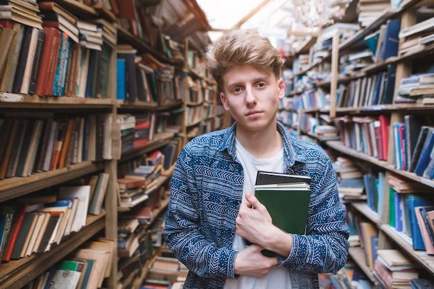 Przystojna młody człowiek pozycja w bibliotece publicznej z książkami w jego rękach i patrzeć w kamerę