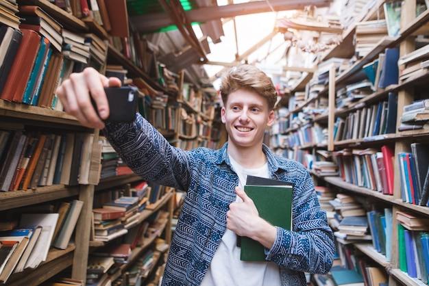 Przystojna młody człowiek pozycja w bibliotece z książkami w jego rękach i robić sephi.