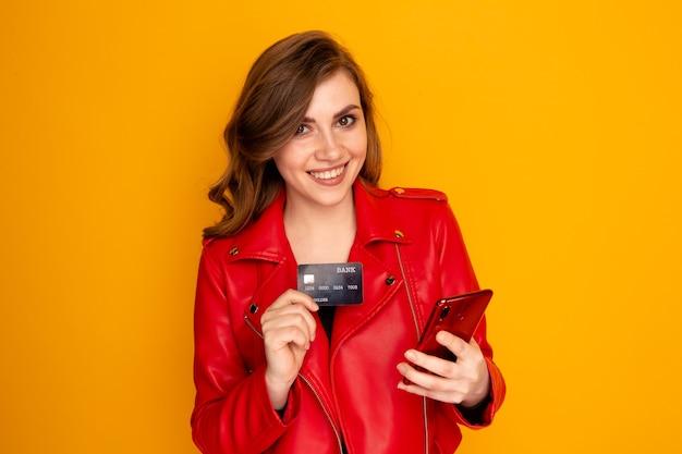 Przystojna osoba płci żeńskiej z kartą kredytową na białym tle na żółtym tle.