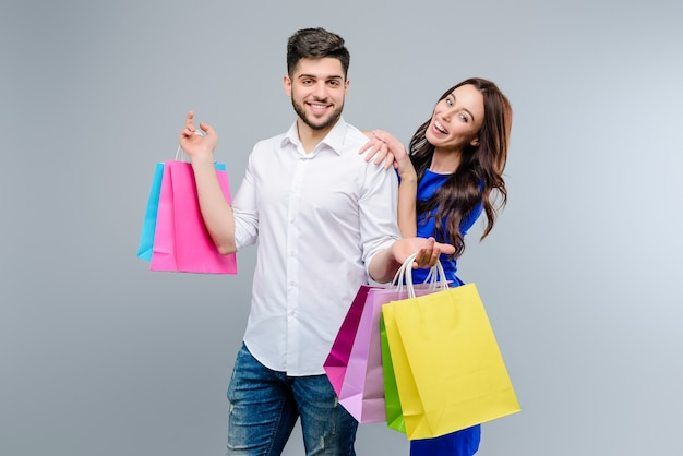 Przystojna para z kolorowymi torba na zakupy od centrum handlowego odizolowywającego nad popielatym