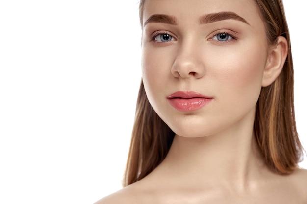 Przystojna, piękna dziewczyna ze zdrową, idealną skórą twarzy, pozowanie na białym tle