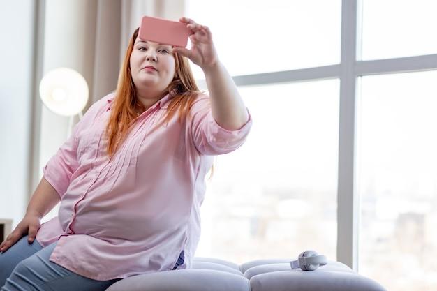 Przystojna, pozytywna kobieta przygląda się sobie na ekranie podczas robienia zdjęcia