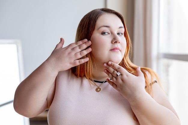 Przystojna, pulchna kobieta dotyka policzka, jednocześnie dbając o swoją skórę